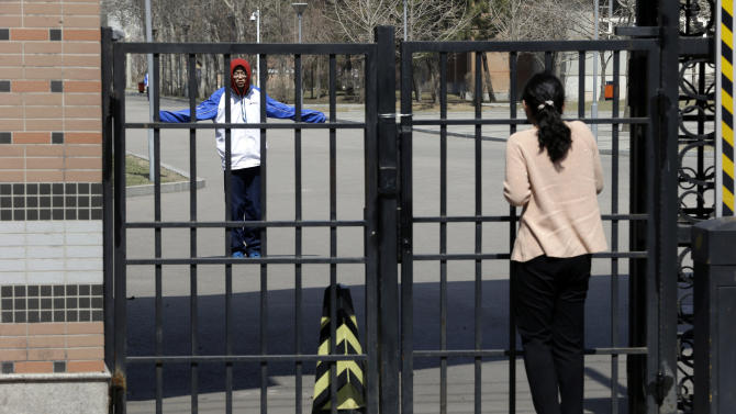 A woman talks to a student in the Northeast Yucai school where one of the victims of Boston Marathon explosions, Lu Lingzi, studied during her high school education, in Shenyang, north eastern China's Liaoning province, Thursday, April 18, 2013. Lu, who was killed in the Boston Marathon blasts, grew up in an intellectual family in a provincial capital with gritty, industrial roots, and graduated from a highly competitive high school that routinely sends students abroad. (AP Photo/Ng Han Guan)