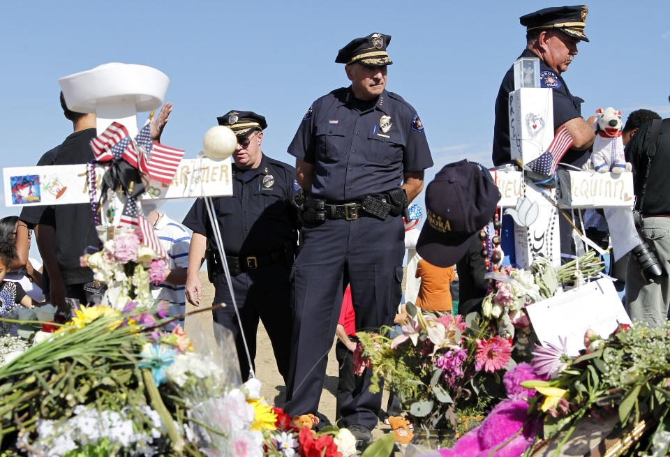 "Aurora Police Chief Daniel Oates, center, looks at the memorial across from the movie theater, Wednesday, July 25, 2012 in Aurora, Colo. Twelve people were killed and over 50 wounded in a shooting attack early Friday at the packed theater during a showing of the Batman movie, ""The Dark Knight Rises."" (AP Photo/Alex Brandon)"