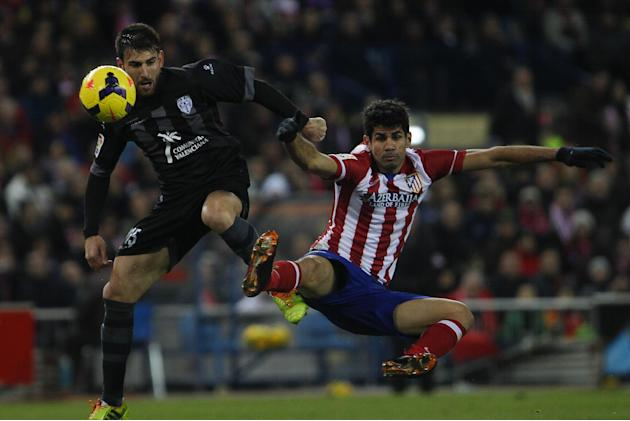 Atletico's Diego Costa, right, competes with Nikos Karampelas from Greece, left, during a Spanish La Liga soccer match between Atletico de Madrid and Levante at the Vicente Calderon stadium in Mad