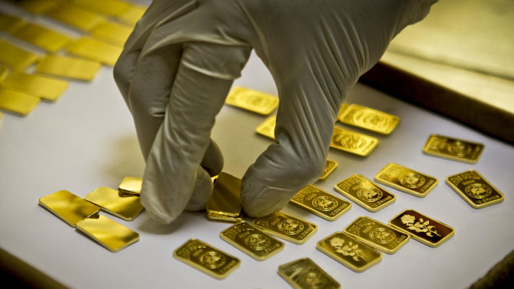 In this Tuesday Oct. 9, 2012 photo, a gold press operator collects 10 gram gold blanks to press them with the logo of the Emirates Gold company in Dubai, United Arab Emirates. Gold prices remained relatively steady in 2012, close to $1,700 an ounce. (AP Photo/Kamran Jebreili)