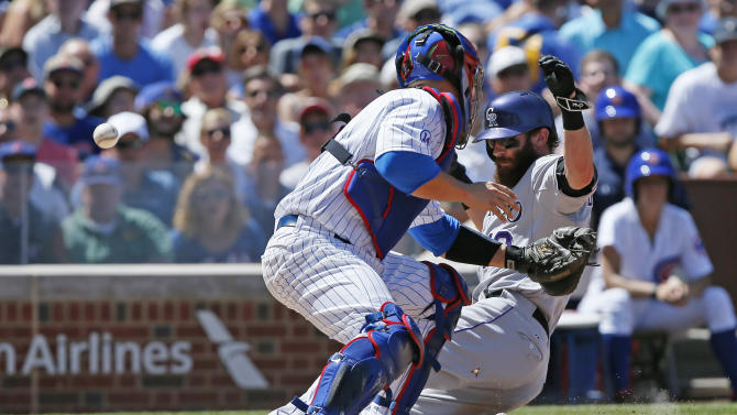 Colorado Rockies' Charlie Blackmon scores on a sacrifice fly by Nolan Arenado as Chicago Cubs catcher David Ross loses the ball during the fourth inning of a baseball game in Chicago, Wednesday, July 29, 2015. (AP Photo/Andrew A. Nelles)