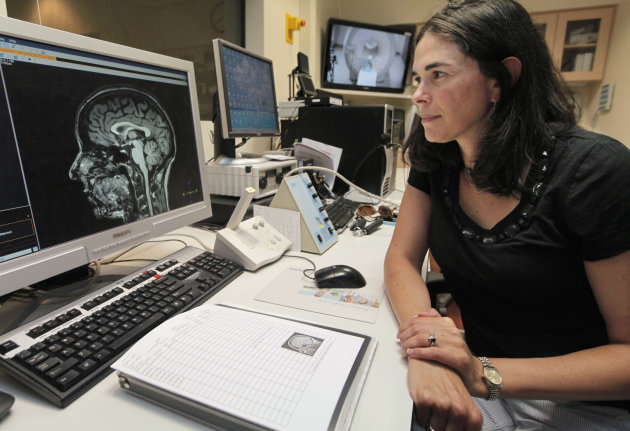 "In this Thursday, July 16, 2012 photo, Sian Beilock, a University of Chicago psychologist, professor and author of the book ""Choke,"" looks at a brain scan from a functional MRI machine in the lab at t"