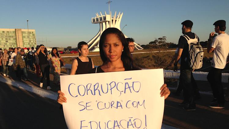 """Caroline Moura poses for a photo holding a sign that reads in Portuguese; """"Corruption is cured with education,"""" at an anti-government protest, in Brasilia, Brazil, Thursday, June 20, 2013.  The 23-year-old business administrator says, """"Corruption is the greatest problem In Brazil. All that money that went into the World Cup is a Matterhorn for the police to look into. If people were more educated we wouldn't have so many corrupt people in power."""" (AP Photo/Marco Sibaja)"""