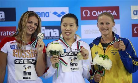 Medallists pose during the women's 50m breaststroke final at the FINA Swimming World Cup in Dubai