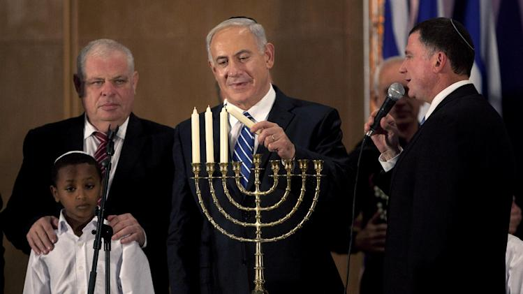 Israeli Prime Minister Benjamin Netanyahu lights candles on the Jewish holiday of Hanukkah during an event with foreign press in Jerusalem, Monday, Dec. 10, 2012.  Netanyahu is accusing the international community of double standards, saying it condemns Israeli settlements in the West Bank but not Palestinians' refusal to renew peace talks or militant group Hamas' call for the end of the Jewish state. (AP Photo/Sebastian Scheiner)