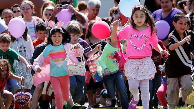 From left, Chloe Chow, 6, and Olivia Jaszczak, 7, race to hunt for Easter eggs at Durham Central Park on Saturday, March 30, 2013 in Durham, N.C.  More than 12,000 eggs were hidden for the event. (AP/The Herald-Sun, Christine T. Nguyen)