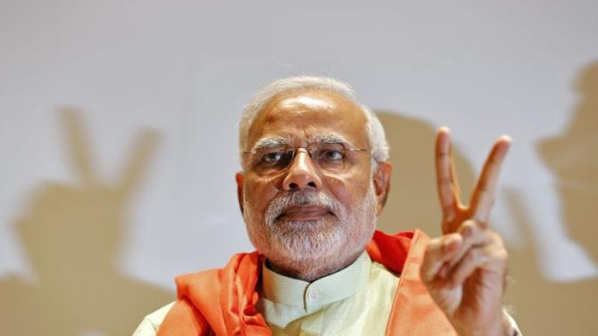Modi, prime ministerial candidate for the BJP, gestures upon his arrival to meet party leaders and workers at Gandhinagar
