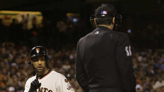San Francisco Giants' Angel Pagan, left, gestures toward umpire Tony Randazzo after striking out against the Milwaukee Brewers during the eighth inning of a baseball game in San Francisco, Tuesday, July 28, 2015. The Brewers won 5-2. (AP Photo/Jeff Chiu)