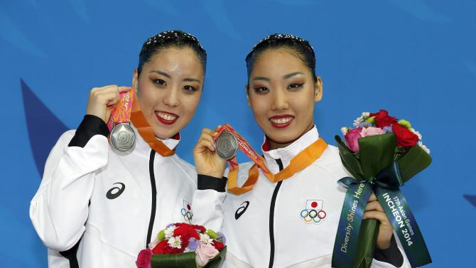 Japan's Yukiko Inui and Risako Mitsui pose with their silver medals after finishing second in the women's duet synchronised swimming competition at Munhak Park Tae-hwan Aquatics Center during the 17th Asian Games in Incheon