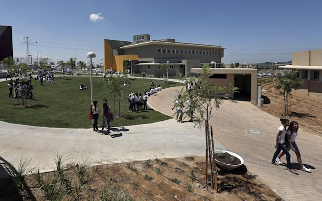 Israeli high-school students walk through the yard next to a new rocketproof school building, in Shaar Hanegev school, near the southern town of Sderot, Israel, Monday, Aug. 27, 2012. The 27.5 million US Dollar structure features concrete walls, reinforced windows and a unique architectural plan all designed specifically to absorb rocket fire.(AP Photo/Tsafrir Abayov)
