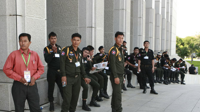 Cambodian security guards take a break while on duty outside the Peace building at the 21st ASEAN Summit in Phnom Penh, Cambodia Tuesday, Nov. 20, 2012. (AP Photo/Apichart Weerawong)