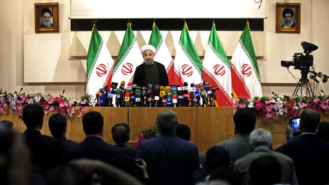 "Iranian newly elected President Hasan Rowhani, listens to the Iranian national anthem, before beginning a press conference, in Tehran, Iran, Monday, June 17, 2013. Rowhani showcases his reformist image by promising a ""path of moderation,"" the easing of nuclear tensions and steps to narrow the huge divide with the United States. He also make clear where he won't go, saying he opposes any halt to uranium enrichment, at the heart of the nuclear standoff. (AP Photo/Ebrahim Noroozi)"