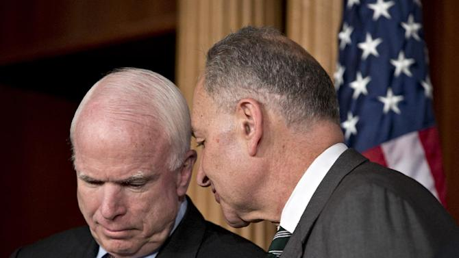 FILE - In this Jan. 28, 2013 file photo, Sen. John McCain, R-Ariz., left, and Sen. Charles Schumer, D-N.Y., confer during a news conference at the Capitol in Washington. Republican McCain is a walking contradiction, assailing President Barack Obama over Libya and Syria one minute, cooperating with him the next on immigration and the budget. As friend or foe, the five-term Arizona senator _ his party's presidential candidate in 2008 _ is giving Washington whiplash. He insists he's consistent. Whatever the issue, McCain is involved in nearly every hot topic.   (AP Photo/J. Scott Applewhite, File)