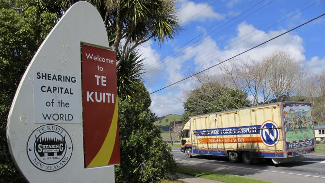 In this photo taken Sept. 25, 2012, a livestock transport truck drives into the self-declared shearing capital of the world Te Kuiti, on New Zealand's central North Island. A Chinese investor this year bought 13 dairy and three cattle and sheep farms in the Waikato region in a sale that was the subject of national debate and legal action. (AP Photo/Nick Perry)