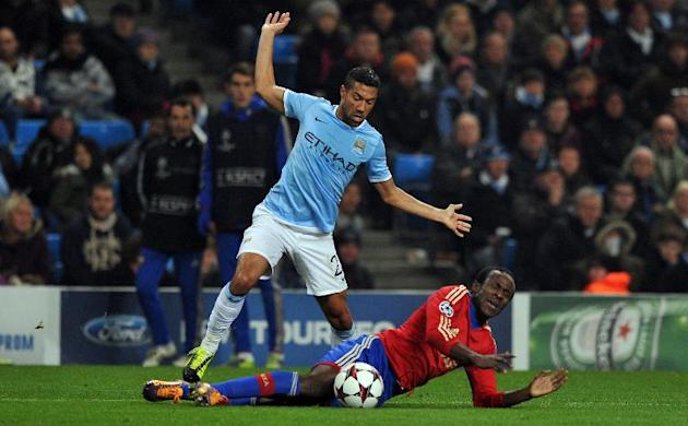Manchester City defender Gael Clichy (L) fouls CSKA Moscow forward Seydou Doumbia for a penalty during the UEFA Champions League football match in Manchester, on November 5, 2013