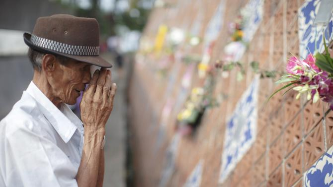 Somjit Bhuddharaj, 58, gestures after placing flowers next to a plaque with the name of his family, who was killed in the 2004 tsunami, at a wave-shaped memorial in Ban Nam Khem