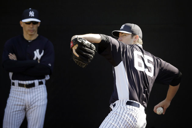 "FILE - In this Feb. 16, 2013 file photo, New York Yankees' Phil Hughes, right, pitches as manager Joe Girardi looks on during a workout at baseball spring training in Tampa, Fla. Hughes could be sidelined for two weeks because of a bulging disk that will be treated with anti-inflammatory medication. ""I'm convinced I'll be symptom free in the next four or five days,"" Hughes said Wednesday, Feb. 20, 2013. (AP Photo/Matt Slocum, File)"