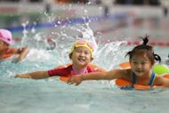 A group of young Chinese children take part in a swimming contest at the National Swimming Centre in Beijing on September 22. China should phase out its unpopular one-child policy and let families have two children by 2015, an influential think-tank with close links to the government has proposed