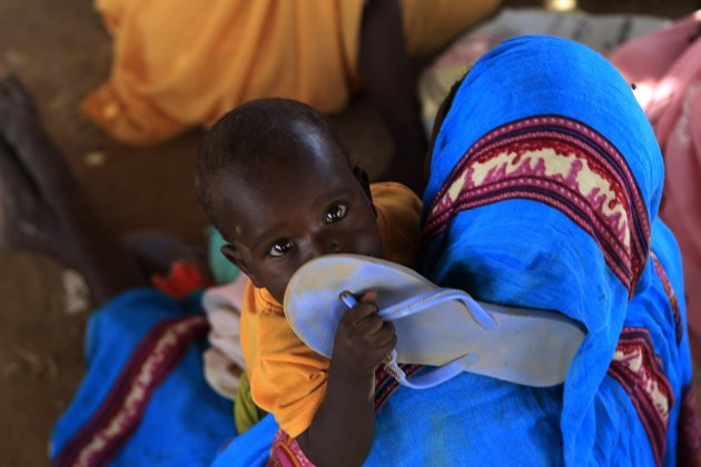 A child holds a slipper as displaced people wait at a food distribution centre as special envoys and diplomats arrive for a meeting to discuss the progress of a peace treaty in Darfur, at Shangli Toba