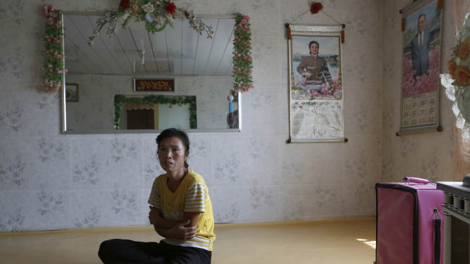 In this photo taken on Sunday, Sept. 23, 2012, North Korean farmer O Yong Ae sits at her home during an interview at the Migok Cooperative farm in Sariwon, North Hwanghae Province, North Korea. Farmers would be able to keep a bigger share of their crops under proposed changes aiming to boost production by North Korea's collective farms, which have chronically struggled to provide enough food for the country's 24 million people. Current rules require them to turn everything over to the state beyond what farmers can keep to feed their families. (AP Photo/Vincent Yu)