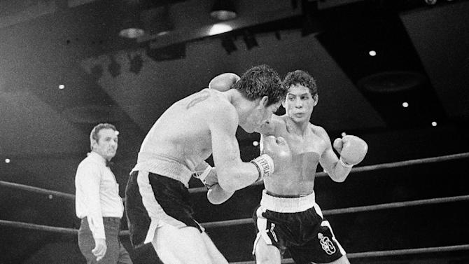 """FILE - In this July 11, 1982 file photo, Luis Loy Jr., left, ducks under a blow by Hector Camacho early in a scheduled 10-round junior lightweight boxing bout at Felt Forum in New York. Hector """"Macho"""" Camacho, a boxer known for skill and flamboyance in the ring, as well as for a messy personal life and run-ins with the police, has died, Saturday, Nov. 24, 2012, after being taken off life support. He was 50. (AP Photo/Elias, File)"""