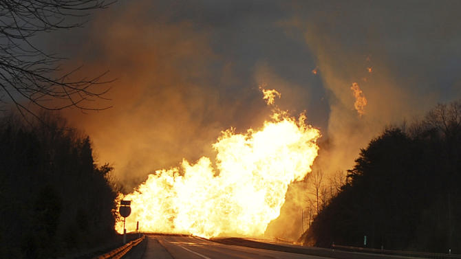 Flames burn from a gas line explosion across Interstate 77 near Sissonville, W.Va., Tuesday, Dec. 11, 2012. At least five homes went up in flames Tuesday afternoon and a badly damaged section of Interstate 77 was shut down in both directions near Sissonville after a natural gas explosion triggered an hour-long inferno that officials say spanned about a quarter-mile. (AP Photo/Joe Long)