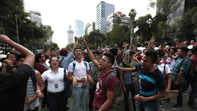 Students shout slogans during a protest march in Mexico City, Tuesday, Sept. 30, 2014. Students of the National Polytechnical Institute (IPN) are protesting over a new set of internal rules and proposed changes in the school's curriculums that will downgrade their status as graduates. (AP Photo/Eduardo Verdugo)