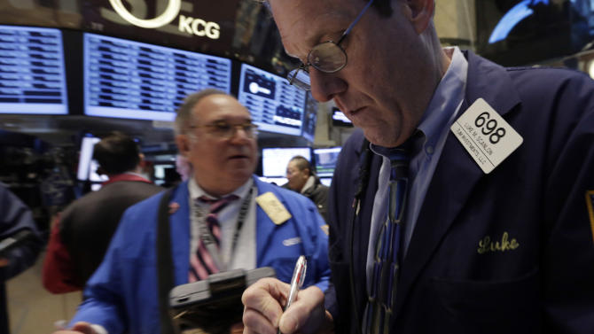 Trader Luke Scanlon, right, works on the floor of the New York Stock Exchange Wednesday, Jan. 29, 2014. Stocks are lower in early trading as weak earnings from several U.S. companies dented investors' confidence. Worries about emerging markets were also coming back after relief faded over an effort by Turkey to shore up its struggling currency. (AP Photo/Richard Drew)