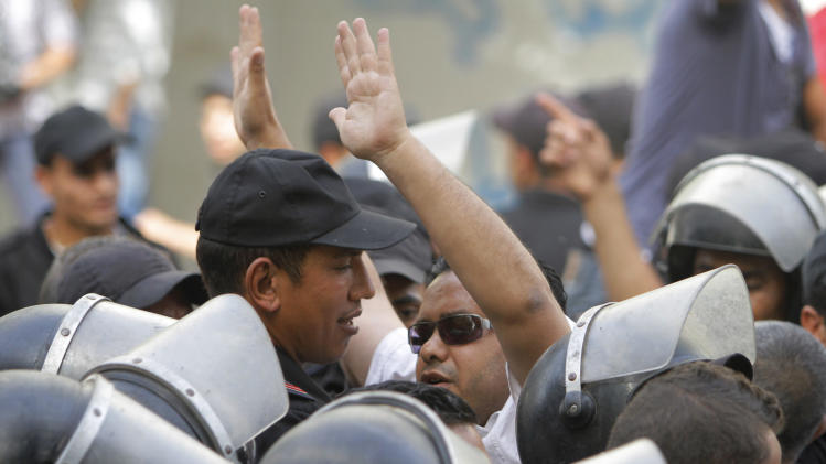 An Egyptian opposition activist shouts anti-Muslim brotherhood slogans as anti-riot soldiers prevent him from getting close to the Shura Council, the upper house of Parliament, during a protest against the new judicial law in Cairo, Egypt, Saturday, May 25, 2013. (AP Photo/ Amr Nabil)
