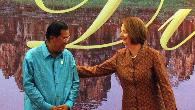 Australian Prime Minister Julia Gillard, right, jokes with Cambodian Prime Minister Hun Sen prior to a group photo before the gala dinner in Phnom Penh, Cambodia, Monday, Nov. 19, 2012. (AP Photo/Apichart Weerawong)