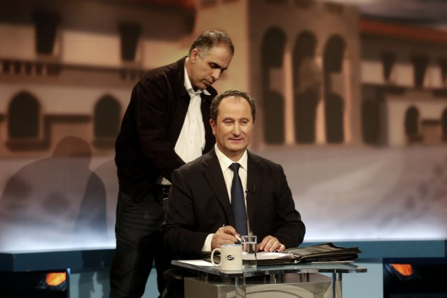 A technician prepares Cyprus left-wing backed independent Presidential candidate Malas for a debate in Nicosia