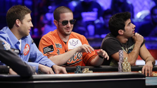 Greg Merson, center, of Laurel, Md., pulls in his winnings on a hand as Jeremy Ausmus, left, of Las Vegas, and Jesse Sylvia, also of Las Vegas, watch during the World Series of Poker Final Table event, Monday, Oct. 29, 2012, in Las Vegas. (AP Photo/Julie Jacobson)