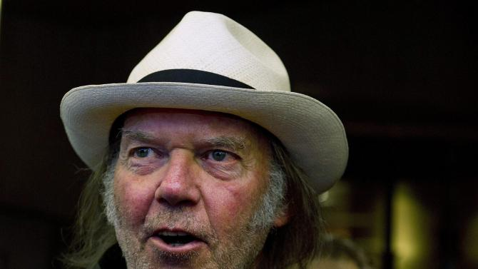 "FILE - In a Monday, Sept., 12, 2011 file photo, musician Neil Young arrives for the film ""Neil Young Journeys"" at the Toronto International Film Festival in Toronto. The organizers of the annual publishing convention, BookExpo America announded Monday, March 19, 2012 that Young will speak June 6, 2012, about his upcoming memoir, ""Waging Heavy Peace,"" scheduled to come out this fall. (AP Photo/The Canadian Press, Nathan Denette, File)"