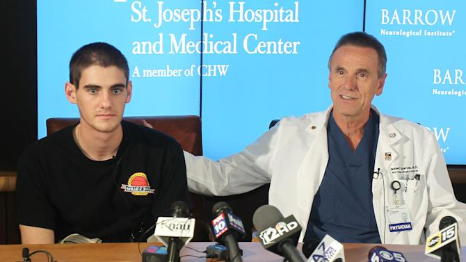 CORRECTS BYLINE TO DEIRDRE HAMILL - Dr. Robert Spetzler, right, talks about Sam Schmid's brain injury during a news conference at Barrow Neurological Institute in Phoenix on Friday, Dec. 23, 2011. Schmid, an Arizona college student believed to be brain dead and poised to be an organ donor, miraculously recovered just hours before doctors were considering taking him off life support. Schmid was critically wounded in an Oct. 19 five-car accident in Tucson. (AP Photo/The Arizona Republic, Deirdre Hamill)  MARICOPA COUNTY OUT; MAGS OUT; NO SALES