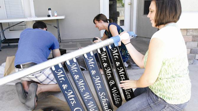 In this Wednesday, Aug. 8, 2012  photo, Andee Waldie, right, helps paint a directional sign with her brother Bradford and soon to be sister-in-law Megan, in Mesa, Ariz.,   Five of the eight siblings of the Waldie family will be married to their spouses on Friday, Aug. 10. While trying to plan wedding dates with out-of-state family and guests, dad Doug Waldie suggested they all marry on the same day. (AP Photo/East Valley Tribune, Tim Hacker) ARIZONA REPUBLIC OUT