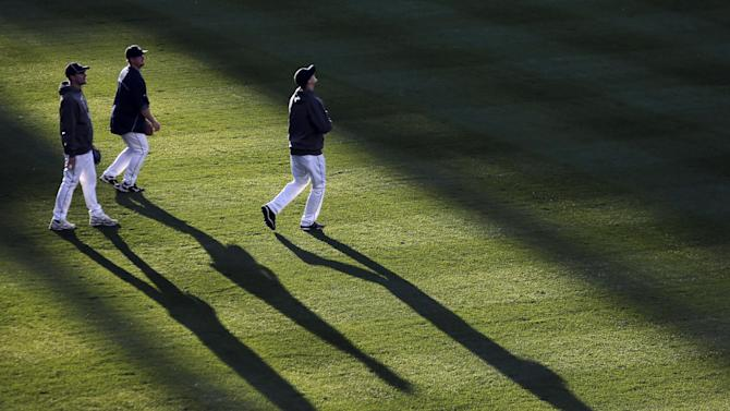 Detroit Tigers players catch fly balls before the start of Game 3 of the American League championship series against the New York Yankees Tuesday, Oct. 16, 2012, in Detroit. (AP Photo/Charlie Riedel)