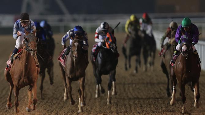 UAE-owned Prince Bishop ridden by William Buick, left, crosses the finish line to win the $ 10,000,000 Dubai World Cup during the Dubai World Cup horse races at Meydan Racecourse in Dubai, United Arab Emirates, Saturday, March 28, 2015. (AP Photo/Kamran Jebreili)