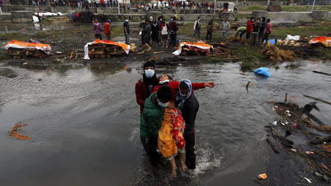 People carry a woman as she fainted after performing the last rites of her family members, who died in Saturday's earthquake, along a river in Kathmandu