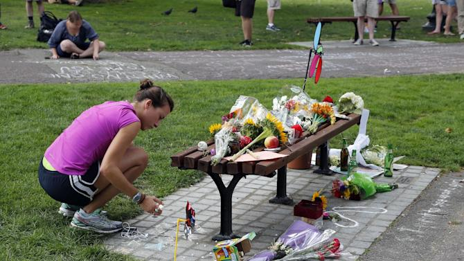 """Women write messages with chalk near a bench at Boston's Public Garden, Tuesday, Aug. 12, 2014, where a small memorial has sprung up at the place where Robin Williams filmed a scene during the movie, """"Good Will Hunting."""" Williams, 63, died at his San Francisco Bay Area home Monday in an apparent suicide. (AP Photo/Elise Amendola)"""