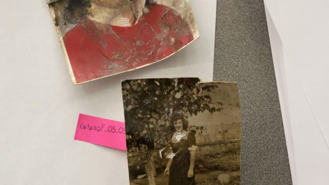 In this Saturday, Feb. 2, 2013 photo, damaged photos belonging to Florence Catania, of Deer Park, N.Y., are evaluated during restoration by Operation Photo Rescue-Hurricane Sandy, at New York's School of Visual Arts. Of all the pictures of Superstorm Sandy's destruction, some of the most lingering for the victims of the storm, are the warped, stained ones that sat on the walls and shelves of flooded homes. The Sandy project promises to be one of Operation Photo Rescue's most expert and ambitious efforts yet. (AP Photo/Richard Drew)