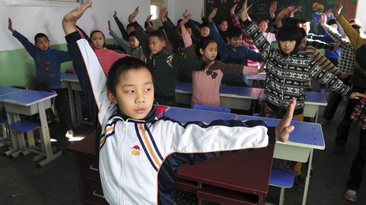 "Pupils practice a set of martial arts ""smog preventing"" exercises in a classroom at a primary school in Shijiazhuang"