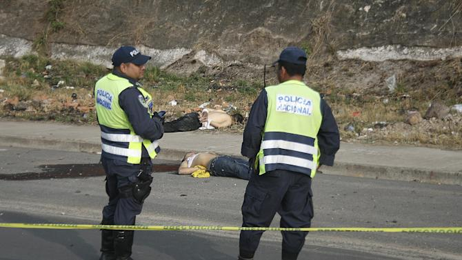 "In this March 23, 2013 photo, police stand next to the bodies of Billy ""Babyface"" Jovel Mejia, 23, and Wilder Javier ""Sadboy"" Alvarado, 20, after they were found dead on the outskirts of the Tegucigalpa, Honduras. Each had a single 9 millimeter gunshot to the head, and their hands were tightly bound. Jovel was missing his right eye, Alvarado his left. Alvarado's mother, Norma, said police had raided her home at least six times in search of her son. (AP Photo/Fernando Antonio)"