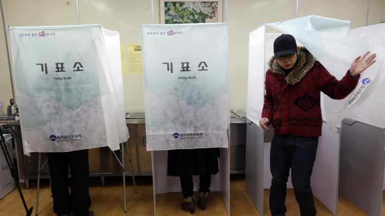 A South Korean woman casts her vote for the presidential election at a local polling station in Seoul, South Korea, Wednesday, Dec. 19, 2012. South Korea's closely contested presidential election  will determine how it will pursue relations with neighbors North Korea and Japan, and if it will have its first female leader. (AP Photo/Lee Jin-man)