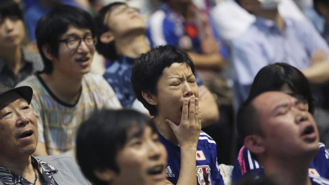 A  Japanese soccer fan yawns as they watch a live broadcast of the Woman's World Cup soccer final match between Japan and the United States at a public viewing venue in Tokyo, Monday, July 6, 2015. (AP Photo/Koji Sasahara)