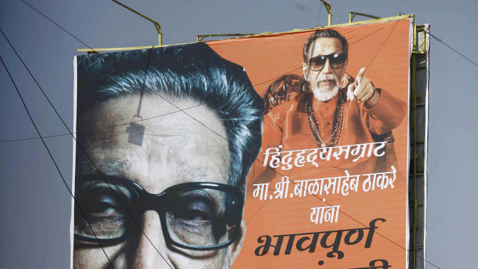 "Indian mourners climb on a billboard of Hindu hardline Shiv Sena party leader Bal Thackeray during his funeral in Mumbai, India, Sunday, Nov. 18, 2012. Thackeray, the extremist leader linked to waves of mob violence against Muslims and migrant workers in India, died Saturday after an illness of several weeks. He was 86. The billboard reads, ""Emotional Homage."" (AP Photo/Rafiq Maqbool)"
