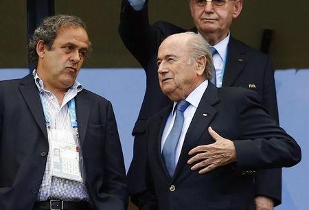 FIFA President Blatter speaks with UEFA President Platini before the 2014 World Cup Group G soccer match between Germany and Portugal at the Fonte Nova arena in Salvador