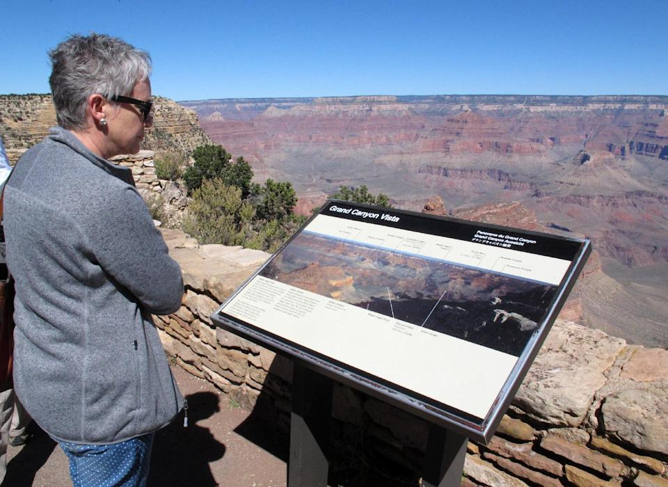 Leana Platt, of Pretoria, South Africa, looks over the South Rim of the Grand Canyon on Monday, Sept. 30, 2013. National parks would shut down Tuesday Oct. 1, 2013 if an agreement is not reached on the federal budget. (AP Photo/Felicia Fonseca)