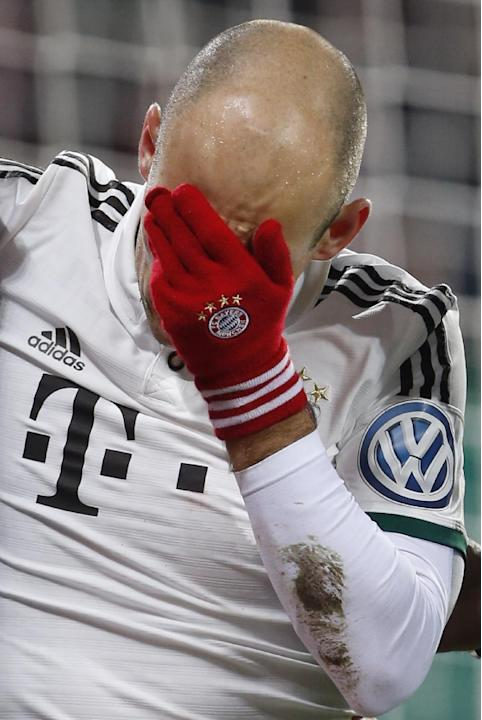 Bayern's Arjen Robben of the Netherlands covers his face after a collision with goalkeeper Marwin Hitz of Switzerland during the German soccer cup third round match between FC Augsburg and FC Baye