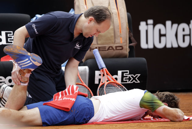 Britain's Andy Murray receives medical care during his match with Spain's Marcel Granollers, at the Italian Open tennis tournament in Rome, Wednesday, May 15, 2013. Murray has retired from his second-