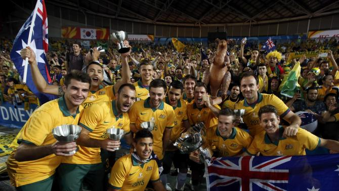 Australia's players pose for pictures with their medals and the Asian Cup trophy after they beat South Korea to win the tournament at the Stadium Australia in Sydney